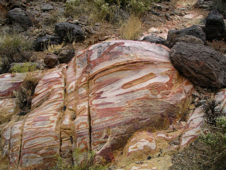A strange rock is the focus here.  It has red and white whorls and banding, and is in the middle of a desert.